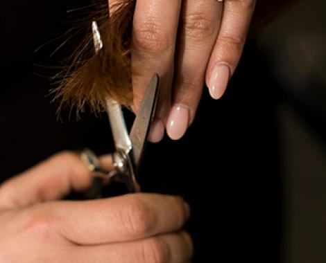 Händer som klipper hår